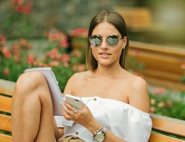 Atrakcyjna młoda kobieta w letnie ubrania i okulary przeciwsłoneczne, trzymając smartfon