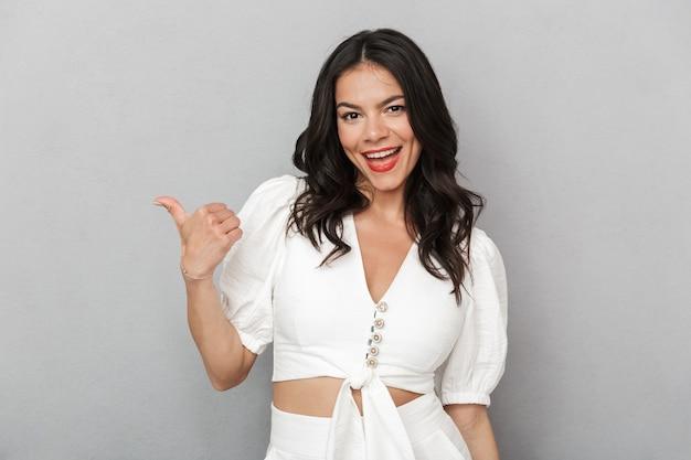 Atrakcyjna młoda kobieta w letnim stroju stojąca na białym tle nad szarą ścianą, wskazująca na miejsce kopiowania