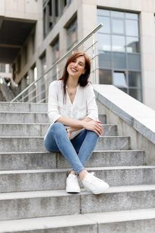 Atrakcyjna młoda kobieta w mieście. biznes pani stojąca w pobliżu centrum biznesowego. zmęczona biznesowa kobieta z białą koszulą w niebieskich dżinsach siedząca relaks na ulicy w pobliżu szklanego budynku w centrum miasta