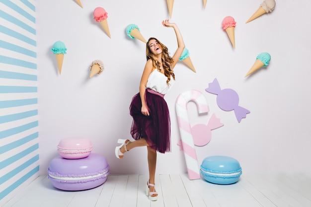 Atrakcyjna młoda kobieta w modnych białych butach taniec z wesołym uśmiechem na imprezie tematycznej. portret całkiem radosnej dziewczyny bawiącej się w pokoju ze słodkim wnętrzem ozdobionym makaronikami.