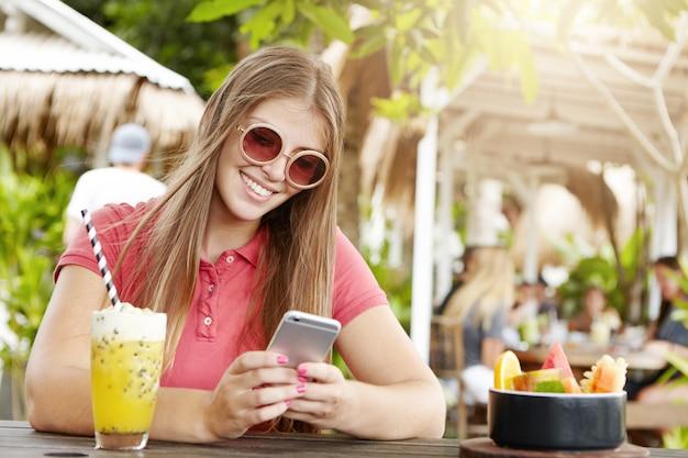 Atrakcyjna młoda kobieta w modnych okrągłych odcieniach siedząca przy barze i wysyłająca sms-y do przyjaciół za pośrednictwem sieci społecznościowych, ciesząca się szybkim połączeniem internetowym i pijąc świeży napój