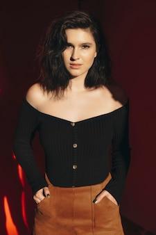 Atrakcyjna młoda kobieta w modnych strojach trzymając ręce w kieszeniach spódnicy i patrząc na kamery, stojąc w ciemnym pokoju