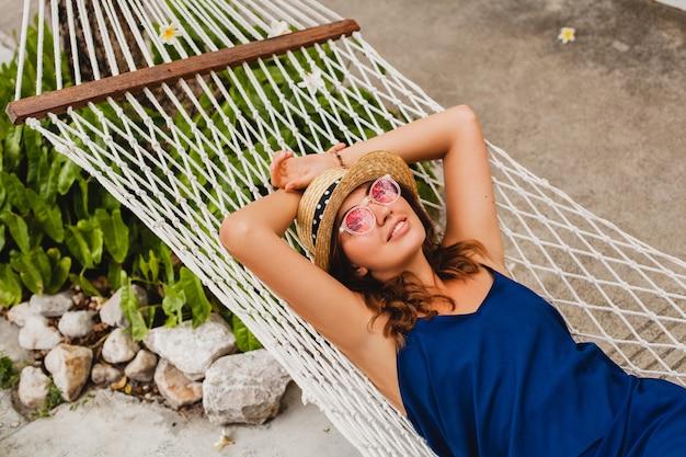 Atrakcyjna młoda kobieta w niebieskiej sukience i słomkowym kapeluszu na sobie różowe okulary, relaksując się na wakacjach, leżąc w hamaku