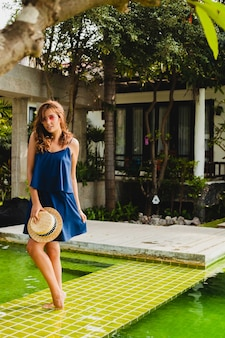 Atrakcyjna młoda kobieta w niebieskiej sukience i słomkowym kapeluszu w różowych okularach chodzenie przy basenie tropikalnej willi spa na wakacjach w letnim stroju, seksowna