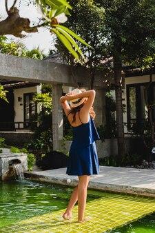 Atrakcyjna młoda kobieta w niebieskiej sukience i słomkowym kapeluszu w różowych okularach przeciwsłonecznych spacerująca po basenie tropikalnej willi spa na wakacjach w letnim stroju, widok z tyłu trzymając się za ręce