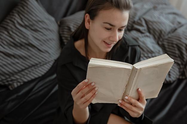 Atrakcyjna młoda kobieta w piżamie relaksuje się w łóżku, czytając książkę