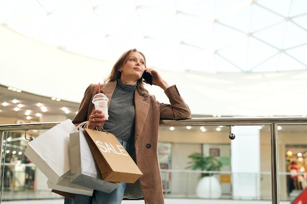Atrakcyjna młoda kobieta w stylowej kurtce, opierając się na poręczy i rozmawiając przez telefon w centrum handlowym