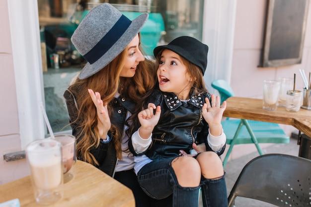 Atrakcyjna młoda kobieta w szarym kapeluszu, wygłupiać się z śliczną córką po wypiciu koktajlu mlecznego.
