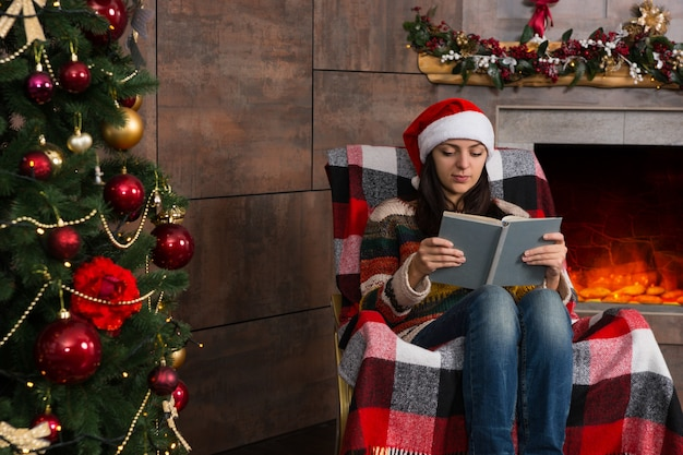 Atrakcyjna młoda kobieta w zabawnym świątecznym kapeluszu czytająca siedząc na bujanym fotelu w pobliżu choinki w salonie z udekorowanym kominkiem