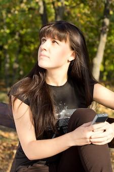 Atrakcyjna młoda kobieta wpatrując się w niebo marzeń, czekając na połączenie na swoim telefonie komórkowym