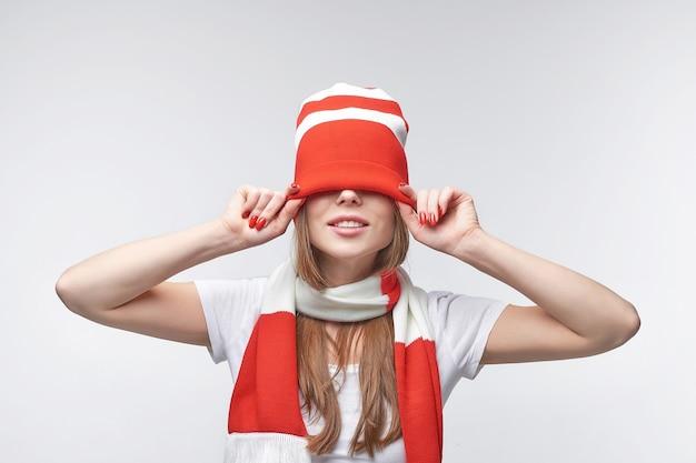 Atrakcyjna młoda kobieta wyciągając czerwono-biały kapelusz z dzianiny na oczy
