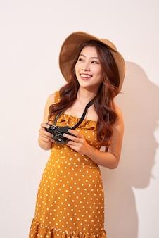 Atrakcyjna młoda kobieta z aparatem fotograficznym w ręku na odosobnionej ścianie beżowej. koncepcja podróży