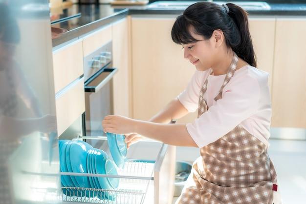 Atrakcyjna młoda kobieta z azji ładuje zmywarkę do szafek w kuchni podczas sprzątania w domu podczas pobytu w domu, korzystając z wolnego czasu na codzienne czynności porządkowe.