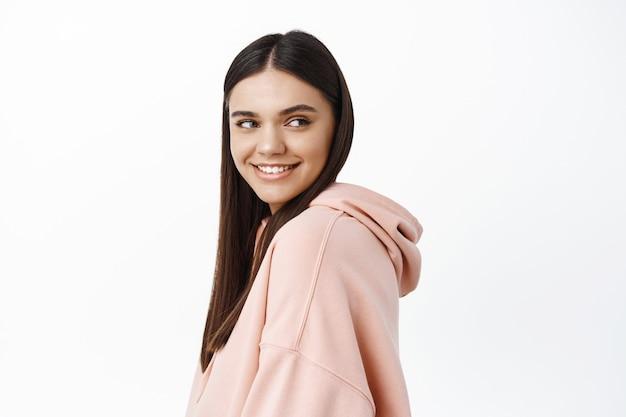 Atrakcyjna młoda kobieta z białymi uśmiechniętymi zębami, odwróć głowę po prawej stronie miejsca kopiowania z zadowoloną i pewną siebie twarzą, stojąc w bluzie z kapturem na białej ścianie