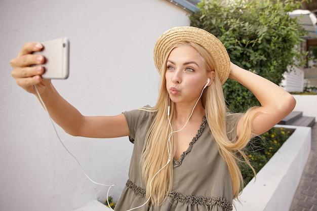 Atrakcyjna młoda kobieta z blond długimi włosami w wiklinowym kapeluszu spaceruje ulicą w słoneczny dzień, robi miny i robi selfie na swoim telefonie