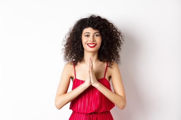 Atrakcyjna młoda kobieta z czerwonymi ustami, wieczorowa sukienka, dziękuję i uśmiechnięta, patrząc wdzięczna gestem namaste, stojąca na białym tle.