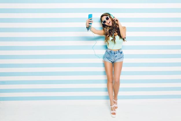 Atrakcyjna młoda kobieta z długimi kręconymi włosami brunetka, w dżinsowych szortach na obcasach, zabawy na pasiastej biało-niebieskiej ścianie. robię selfie, słucham muzyki w słuchawkach, podekscytowany.