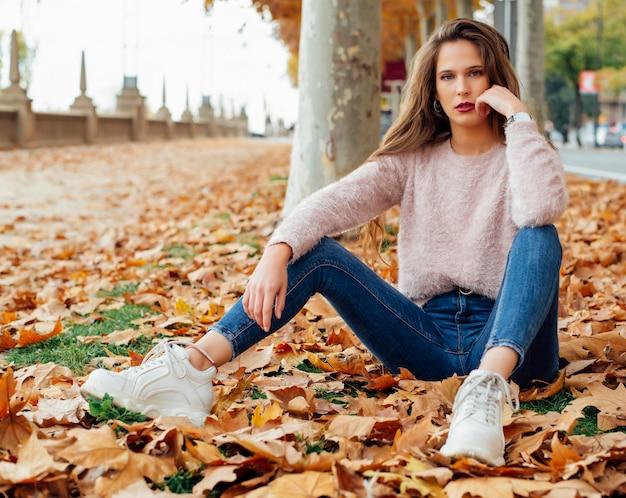 Atrakcyjna młoda kobieta z długimi włosami i różowym pulowerem pozuje do kamery w parku jesienią.