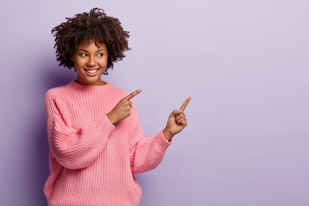 Atrakcyjna młoda kobieta z kręconymi włosami, zębowym uśmiechem, zdrową ciemną skórą, odkłada na bok wolną przestrzeń, demonstruje coś niesamowitego na fioletowej przestrzeni kopii, nosi różowy sweter