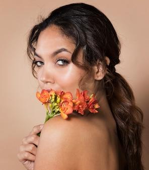 Atrakcyjna młoda kobieta z kwiatami na jej ramieniu