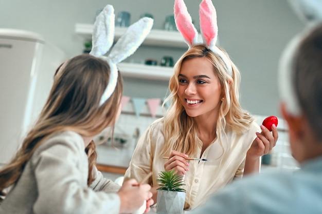 Atrakcyjna młoda kobieta z małą ładną dziewczyną i chłopcem przygotowują się do obchodów wielkanocy. szczęśliwa rodzina w uszach króliczka spędza razem czas przed wielkanocą podczas malowania jajek.