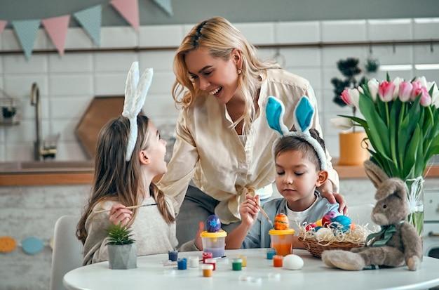 Atrakcyjna młoda kobieta z małą śliczną dziewczyną i chłopcem przygotowują się do obchodów wielkanocy. szczęśliwa rodzina w uszach królika spędza razem czas przed wielkanocą podczas malowania jajek.