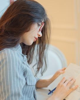 Atrakcyjna młoda kobieta z piórem w ręku, myśląc o planach i pisania listy zrobić w notatniku, ciesząc się rekreacji w stylowej kawiarni