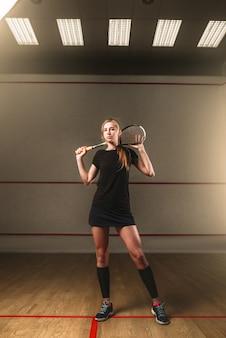 Atrakcyjna młoda kobieta z rakietą do squasha, kryty klub treningowy