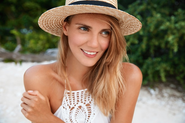 Atrakcyjna młoda kobieta z rozmarzonym pozytywnym wyrazem twarzy, ubrana w modny kapelusz i letnią białą sukienkę, zamyślona patrzy w dal, planuje coś na następny dzień, dobrze wypoczywa za granicą