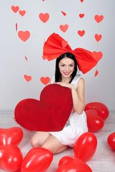 Atrakcyjna młoda kobieta z wielkim sercem i balonami w pokoju na walentynki
