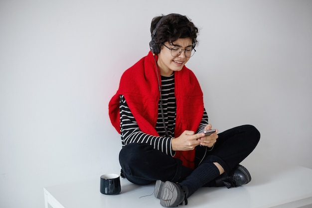 Atrakcyjna młoda kręcona brunetka hipster kobieta z krótką modną fryzurą trzymając telefon komórkowy w dłoniach podczas słuchania muzyki w słuchawkach z wielką przyjemnością
