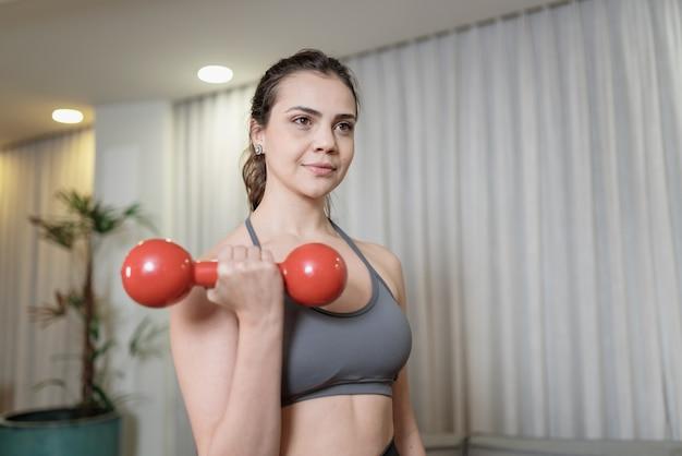 Atrakcyjna młoda łacińska kobieta ćwiczy w domu. pojęcie zdrowego stylu życia.