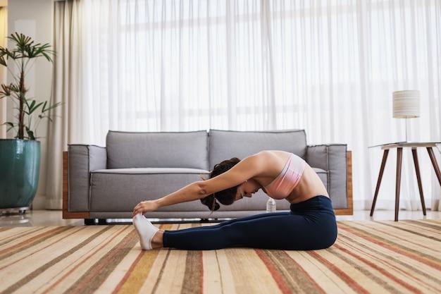 Atrakcyjna młoda latynoska kobieta robi joga rozciągająca jogę w domu