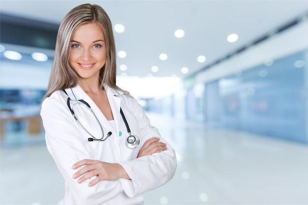 Atrakcyjna młoda lekarka z niewyraźnym wnętrzem szpitala na tle