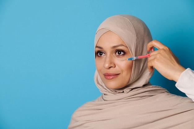 Atrakcyjna młoda muzułmanka z doskonałym makijażem i czystą zdrową skórą, pozuje ze strzykawką w pobliżu twarzy