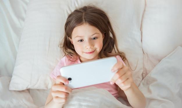 Atrakcyjna młoda nastolatka leży na łóżku, uśmiechając się i patrząc na laptopa na czacie z przyjaciółmi. surfowanie po internecie, wysyłanie wiadomości lub praca w trybie domowym
