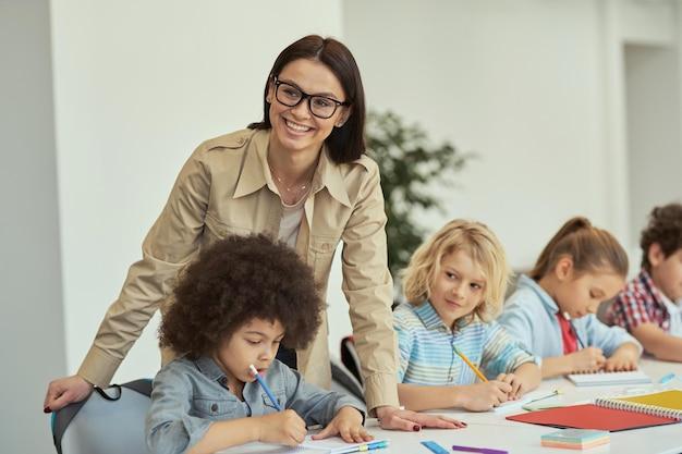Atrakcyjna młoda nauczycielka w okularach uśmiecha się do kamery, pomagając małym uczniom dzieciom