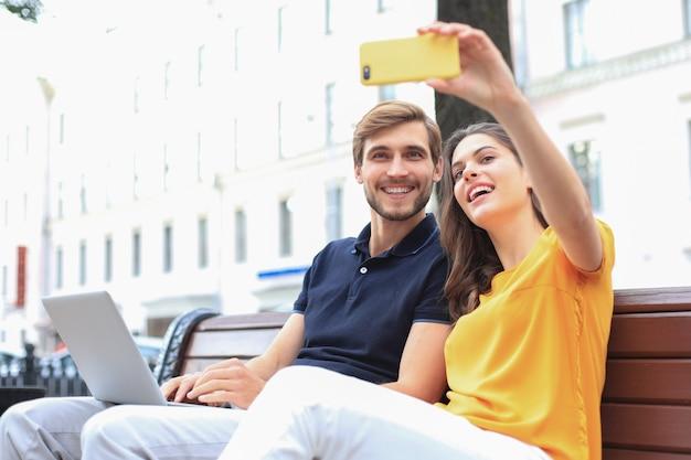 Atrakcyjna młoda para siedzi na ławce i przy selfie na smartfonie.