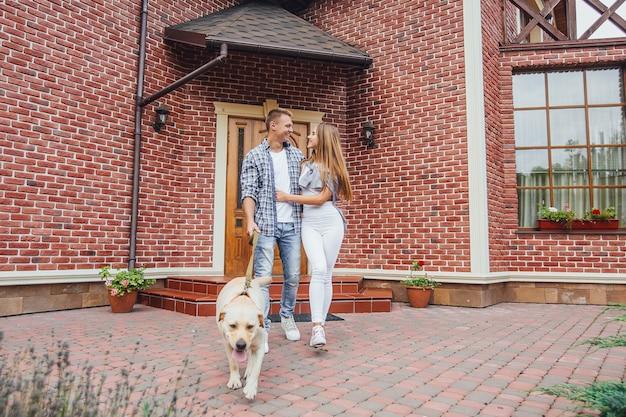 Atrakcyjna młoda para z labradorem przed swoim nowym pięknym domem