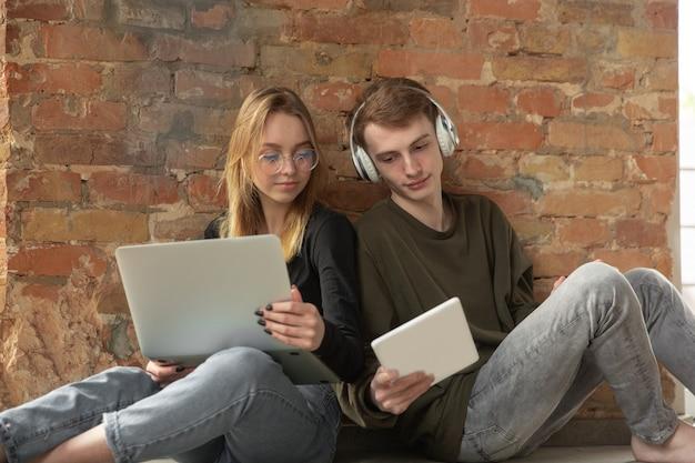 Atrakcyjna młoda para za pomocą urządzeń razem, tablet, laptop, smartfon, słuchawki bezprzewodowe. komunikacja, koncepcja gadżetów. technologie łączące ludzi w samoizolacji. styl życia w domu.