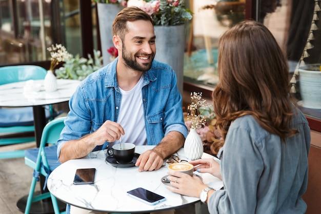 Atrakcyjna młoda para zakochana jedząca lunch siedząc przy stoliku kawiarnianym na świeżym powietrzu, pijąca kawę, rozmawiającą