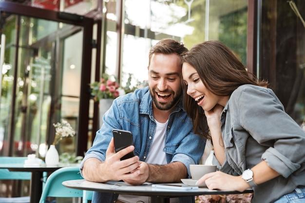 Atrakcyjna młoda para zakochana jedząca lunch siedząc przy stoliku kawiarnianym na świeżym powietrzu, przy użyciu telefonu komórkowego