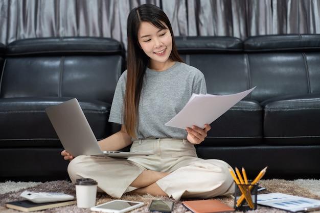 Atrakcyjna młoda piękna azjatycka kobieta przedsiębiorca lub wolny strzelec pracujący w domu z laptopem, raportami biznesowymi i komunikacją online na kanapie w salonie, pracując przy koncepcji dostępu zdalnego.