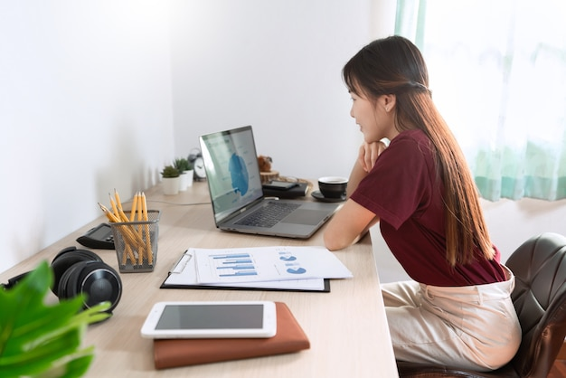 Atrakcyjna młoda piękna azjatykcia kobieta pracuje z laptopem i dokumentem podczas gdy siedzący przy indoors żywym izbowym biurem jako freelancer, e-trenuje działanie, zdalnie lub pracuje od domowego pojęcia.
