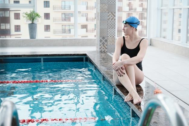 Atrakcyjna młoda pływaczka w niebieskiej czapce siedzi na krawędzi basenu i patrząc na wodę w basenie
