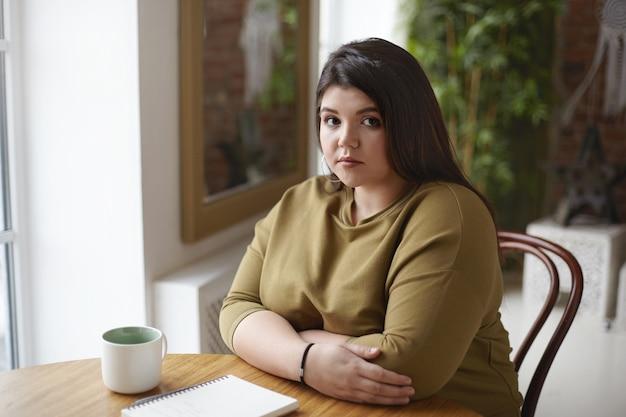 Atrakcyjna młoda pulchna kobieta z nadwagą pije kawę w kawiarni z kubkiem i zeszytem na stole, wpatrując się poważnie, robiąc ważne notatki w dzienniku, planując lub szkicując