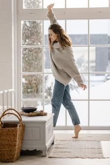 Atrakcyjna młoda radosna kobieta w przytulnym swetrze bawić się tańcząc w pobliżu okna w domu. wypoczynek w czasie wakacji. nieostrość
