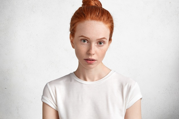 Atrakcyjna młoda rudowłosa kobieta o piegowatej skórze i poważnym wyglądzie, ubrana w zwykłą białą koszulkę, modelki na białej betonowej ścianie.