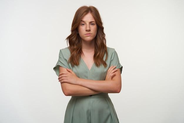 Atrakcyjna młoda rudowłosa kobieta stoi ze skrzyżowanymi rękami na piersi, unosząc brwi i patrząc z niedowierzaniem