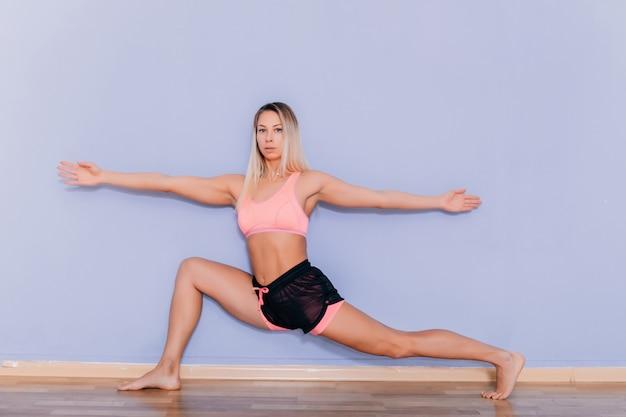 Atrakcyjna młoda seksowna kobieta w sportswear pozuje na szarym tle. szczupła i zdrowa blondynka modelki w studio pozowanie do aparatu.